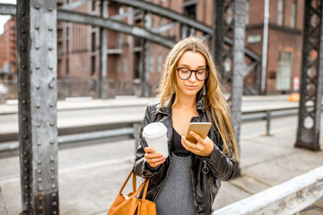 Lifestyle portrait of a stylish business woman with smartphone and coffeecup walking outdoors on the old iron bridge