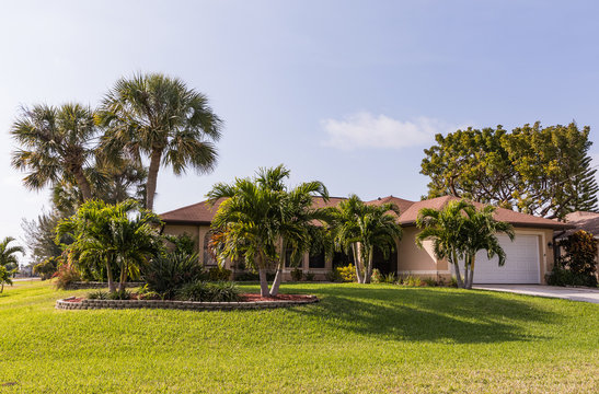 Typical Southwest Florida concrete block and stucco home in the countryside with palm trees, tropical plants and flowers, grass lawn and pine trees. Florida