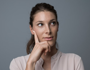 Confident woman thinking with hand on chin