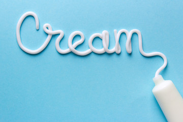 The word is written with a cream from a tube on a blue background. Mock-up white tube of cream