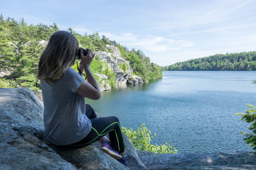 Woman taking photo with DSLR of beautiful nature scenery