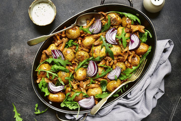 Oven baked new potato with mushrooms,onion and arugula.Top view.