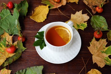 Tea with lemon on the table with autumn leaves