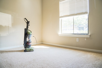 Modern vacuum cleaner connects to power outlet at the corner of clean apartment bedroom with window view, natural light and vacuuming rough carpet. Typical apartment bedroom detail in America.