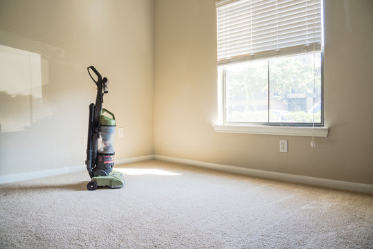 Modern vacuum cleaner stands at the corner of clean apartment bedroom with window view, natural light and vacuuming rough carpet. Typical apartment bedroom detail in America.