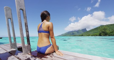 Wall Mural - Bikini woman enjoying tropical vacation sitting after swim on overwater bungalow resort deck at luxury hotel in Tahiti, French Polynesia. Summer tropical holidays lifestyle. RED EPIC SLOW MOTION.