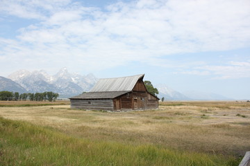 Rustic cabin in grass against a mountain