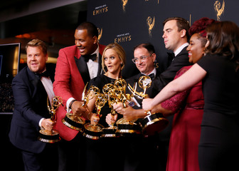 "Host James Corden holds an Emmy Award for Outstanding Variety Special for ""Carpool Karaoke"" as he jokingly jumps into a photo to pose with Samantha Bee and the other winners from ""Full Frontal With Samantha Bee Presents Not The White House Correspondents\"