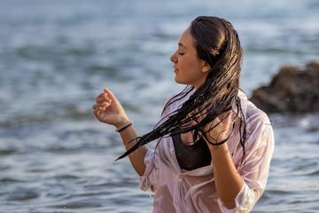 Chica joven con camisa blanca bañándose en el mar al atardecer y jugando con su pelo largo moreno.