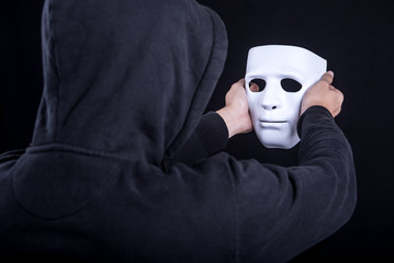 Mystery man holding and looking at white mask