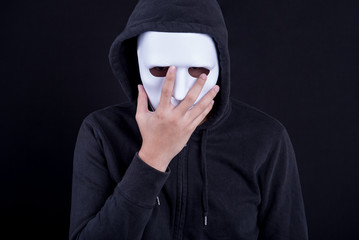 Mystery man holding and wearing white mask for hide his face. Anonymous social masking or halloween concept.