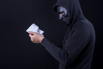 Mystery man wearing black mask holding and looking at white mask. Anonymous social masking or halloween concept.