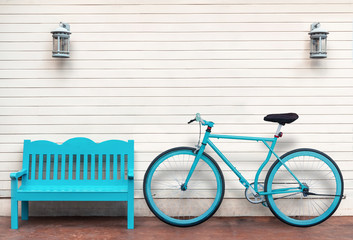Bicycle and bench beside wooden wall