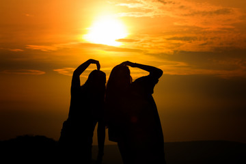 Silhouette of couple in love watching a sunset on the mountains, moment of reflection