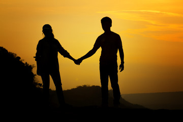 Silhouette couple's holding hand for travelers on sunrise