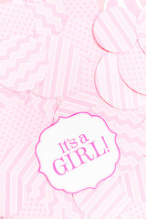 It's a girl sign at the baby shower party.  Pink patterns background.  Baby shower celebration concept
