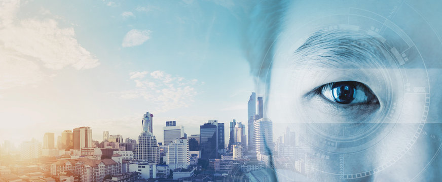 Double exposure, Asian businessman's eye, with futuristic technology visual effect and city skyline in sunrise background