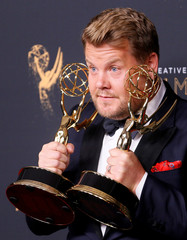 """Host James Corden poses with his two Emmy Awards for Outstanding Special Class Program for """"70th Annual Tony Awards"""" and Outstanding Variety Special for """"Carpool Karaoke"""" backstage at the 2017 Creative Arts Emmy Awards in Los Angeles"""