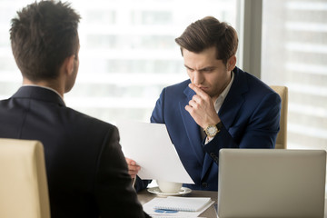 Doubting businessman reading contract document with suspicion when sitting at desk in front of business partner. Entrepreneur unsure in terms of agreement, feeling skeptical because of financial plan
