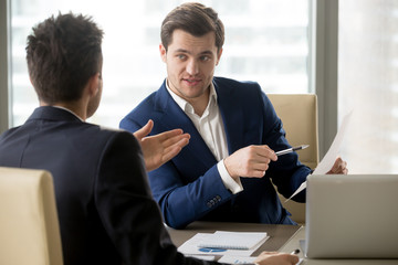 Successful businessman clarifying provisions of contract with business partner, discussing terms of agreement, explaining strategy or financial plan. HR manager asking job candidate about his resume