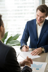 Smiling businessman putting signature on contract, accepting profitable offer, satisfied with deal conditions, approving companies partnership while sitting in front of business partner at negotiation
