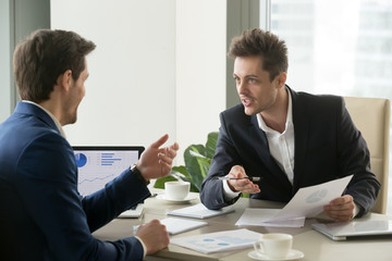 Two successful businessmen discussing company financial strategy, analyzing economic indicators, planning profitability and stock value growth while sitting at desk in office during business meeting