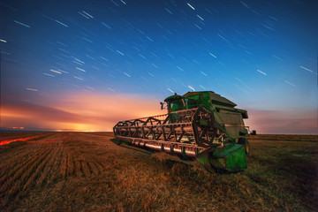 Combine harvester machine working in a wheat field, sunset and stars abstract