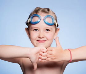 funny girl in glasses for swimming on a blue background