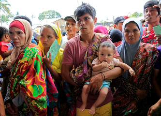 Evacuees wait for their names to be called to get relief goods, after fleeing to an evacuation centre to avoid the fighting in Marawi between the government troops and Islamic State-linked militants, in Saguiaran town