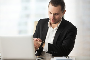 Businessman looking at wristwatch at work desk in office. Busy project manager impatient for work day to end, business partners or job candidates are late to meeting, waiting for interview to start.