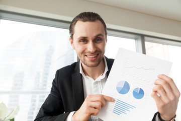 Young businessman in modern office holding and proudly showing positive financial report document with happy smile, pleased with successful stock investment profit stats. Finance success concept.