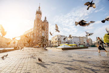 Autocollant pour porte Cracovie View on the central square and famous st. Marys basilica with pigeons flying during the sunrise in Krakow, Poland