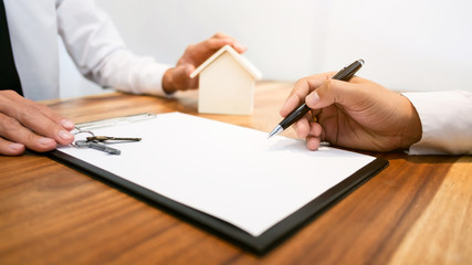 Real Estate agent with customer making contract signature buy / rent a house