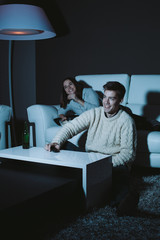 Young couple in love watching a comedy on TV