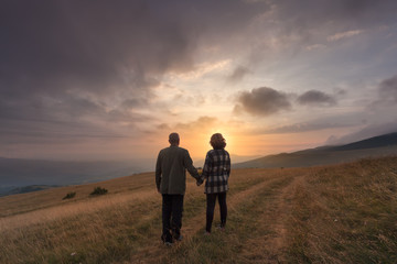 Senior couple hold hands on hill at idyllic sunset