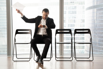 Distraught impatient businessman looking at wristwatch and yelling in anger because of tedious wait. Hand with resume document thrown in the air. Unhappy job candidate or businessman waiting too long.