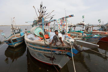 Fisherman Abdul Hameed, a Rohingya Muslim living in Pakistan, sits on a fishing boat at the fish harbour in Ibrahim Hydri in Karachi
