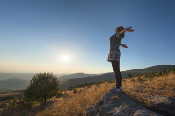 Young woman feel free on beautiful mountain at sunset