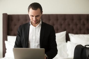 Young smiling businessman working on laptop in bedroom. Freelance entrepreneur remotely works from home, in hotel room while traveling. Business traveler finalizing work project, browsing web concept.