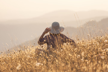 Young woman in mountain sitting on idyllic field at sunset