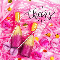Pink and Gold Mini individual bottles for toasting of champagne with confetti and tinsel. Flat lay.  Holiday concept