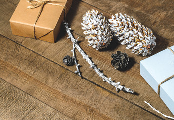 Boxes with gifts, cones, free space  on a wooden background