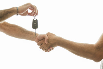 Car salesman handing over the keys for a new car to a young businessman . Handshake between two business people. Focus on a key. sales and handshake isolated on white background