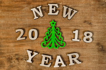 Green Christmas tree and sign 2018 New year from wooden letters, symbol of wooden texture background. Happy new year 2018 backdrop.Greeting card