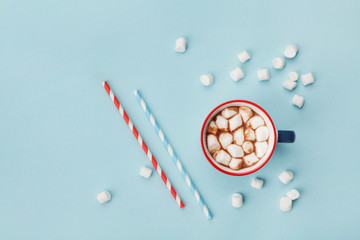 Mug of hot cocoa or chocolate and straw on turquoise table top view. Flat lay.