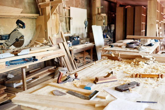 Interior of spacious messy workshop: table with wooden planks, woodworking tools and sawdust on foreground, no people
