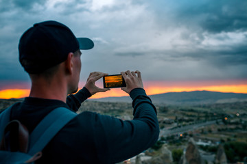 A tourist from a height looking at the sunset over the town of Goreme in Turkey makes a photo. Cappadocia. Tourism, rest, rest.