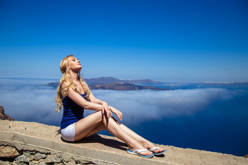 Fotobehang portrait of a beautiful young woman resting on nature on a Greek island Santorini