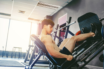 Fitness young man exercising using rowing machine in the gym