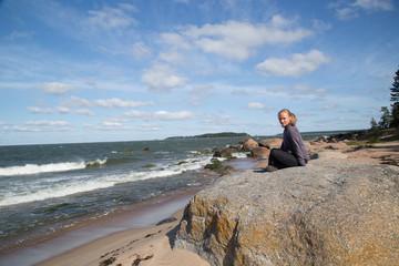 Pretty and natural woman enjoys the nature at the wild beach in the Lahemaa National Park, Käsmu, on the horizon the island Kuradisaar, stormy, summer